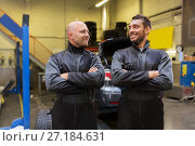 Купить «auto mechanics or tire changers at car shop», фото № 27184631, снято 21 сентября 2017 г. (c) Syda Productions / Фотобанк Лори