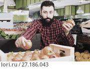 Купить «Shop assistant demonstrating persimmons in grocery store», фото № 27186043, снято 15 ноября 2016 г. (c) Яков Филимонов / Фотобанк Лори