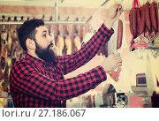 Купить «Young male customer examining sausages in butcher's shop», фото № 27186067, снято 16 ноября 2016 г. (c) Яков Филимонов / Фотобанк Лори