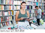 Купить «Interested teenager girl customer reading book», фото № 27187859, снято 16 сентября 2016 г. (c) Яков Филимонов / Фотобанк Лори