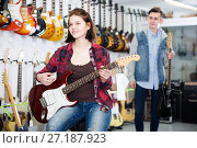 Купить «Female and male teenagers customers examining electric guitars», фото № 27187923, снято 14 февраля 2017 г. (c) Яков Филимонов / Фотобанк Лори