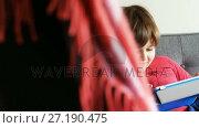 Купить «Boy using digital tablet in living room 4k», видеоролик № 27190475, снято 17 января 2020 г. (c) Wavebreak Media / Фотобанк Лори
