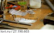 Купить «Goldsmith working at desk in workshop 4k», видеоролик № 27190603, снято 9 апреля 2020 г. (c) Wavebreak Media / Фотобанк Лори