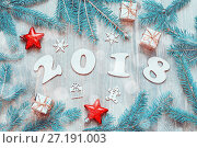 Купить «Happy New Year 2018 background with 2018 figures, Christmas toys, blue fir tree branches. New Year 2018 still life», фото № 27191003, снято 29 ноября 2016 г. (c) Зезелина Марина / Фотобанк Лори