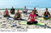 Купить «Group of sporty people practicing yoga in lotus positions on ocean beach», видеоролик № 27194059, снято 22 июня 2017 г. (c) Яков Филимонов / Фотобанк Лори