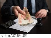 Купить «Бизнесмен сидит за столом с документами и протягивает пачку денег», эксклюзивное фото № 27194251, снято 6 ноября 2017 г. (c) Игорь Низов / Фотобанк Лори