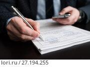 Купить «Бизнесмен подписывает документы держа в руках мобильный телефон», эксклюзивное фото № 27194255, снято 6 ноября 2017 г. (c) Игорь Низов / Фотобанк Лори