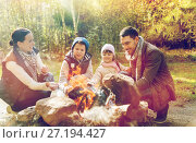 Купить «happy family roasting marshmallow over campfire», фото № 27194427, снято 27 сентября 2015 г. (c) Syda Productions / Фотобанк Лори