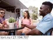 Купить «friends with drinks sitting at table at food truck», фото № 27194707, снято 1 августа 2017 г. (c) Syda Productions / Фотобанк Лори