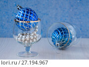 Купить «Thread of white pearls in a glass and a blue Christmas ball on a table», фото № 27194967, снято 28 октября 2017 г. (c) Катерина Белякина / Фотобанк Лори