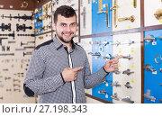 Купить «Young man choosing on best door handles», фото № 27198343, снято 5 апреля 2017 г. (c) Яков Филимонов / Фотобанк Лори