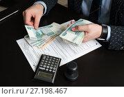 Купить «Руководитель предприятия подсчитывает деньги для оплаты налога на фоне декларации», эксклюзивное фото № 27198467, снято 6 ноября 2017 г. (c) Игорь Низов / Фотобанк Лори