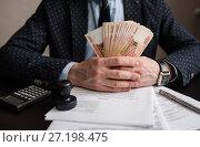 Купить «Мужчина в костюме сидит за столом с документами и держит в руках пятитысячные деньги», эксклюзивное фото № 27198475, снято 6 ноября 2017 г. (c) Игорь Низов / Фотобанк Лори