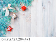 Купить «New Year and Christmas background. Christmas toys, blue fir tree branches on the wooden background. Festive New Year still life», фото № 27204471, снято 8 мая 2017 г. (c) Зезелина Марина / Фотобанк Лори