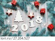 Купить «Happy New Year 2018 background with 2018 figures, Christmas toys, blue fir tree branches. New Year 2018 festive still life», фото № 27204527, снято 29 ноября 2016 г. (c) Зезелина Марина / Фотобанк Лори