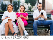 Купить «Young people are focusing on smartphones during a together walking outdoors.», фото № 27204663, снято 18 октября 2017 г. (c) Яков Филимонов / Фотобанк Лори