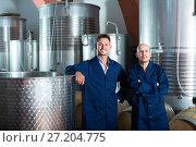 Купить «Two happy men in uniforms standing in winery fermentation compartment», фото № 27204775, снято 15 сентября 2019 г. (c) Яков Филимонов / Фотобанк Лори