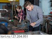 Купить «Master is standing near vise equipment», фото № 27204951, снято 10 октября 2017 г. (c) Яков Филимонов / Фотобанк Лори