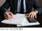 Купить «Бизнесмен считает на калькуляторе и делает пометки в документах», эксклюзивное фото № 27210283, снято 6 ноября 2017 г. (c) Игорь Низов / Фотобанк Лори