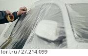 Купить «Man glue duct tape on the car - painting car door», видеоролик № 27214099, снято 25 апреля 2018 г. (c) Константин Шишкин / Фотобанк Лори
