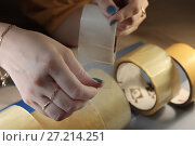 Купить «Женские руки держат прозрачный канцелярский скотч», фото № 27214251, снято 18 ноября 2017 г. (c) Юлия Юриева / Фотобанк Лори