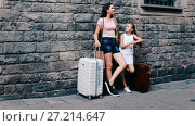 Купить «Young woman and little girl traveler with suitcase leaning against stone wall», видеоролик № 27214647, снято 23 августа 2017 г. (c) Яков Филимонов / Фотобанк Лори