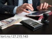 Купить «Деньги и калькулятор на фоне мужчины работающего за планшетом. Фокус на калькуляторе», эксклюзивное фото № 27215143, снято 6 ноября 2017 г. (c) Игорь Низов / Фотобанк Лори
