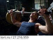 Купить «man doing chest press on exercise machine in gym», фото № 27216959, снято 2 июля 2017 г. (c) Syda Productions / Фотобанк Лори