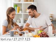 Купить «couple with smartphones having breakfast at home», фото № 27217123, снято 19 октября 2017 г. (c) Syda Productions / Фотобанк Лори