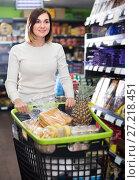 Купить «smiling girl customer looking for food supplies for week in supermarket», фото № 27218451, снято 23 ноября 2016 г. (c) Яков Филимонов / Фотобанк Лори