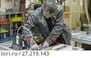 Купить «The electrician assembles and adjusts the electrical control panel. Works on assembling the electrical circuit of a metal-cutting machine.», видеоролик № 27219143, снято 15 июня 2017 г. (c) Андрей Радченко / Фотобанк Лори