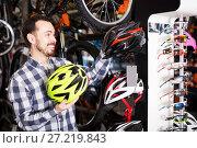 Купить «Man decide on helmet for cycling», фото № 27219843, снято 21 января 2018 г. (c) Яков Филимонов / Фотобанк Лори