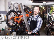 Купить «Man change a wheel on a bicycle», фото № 27219863, снято 18 октября 2018 г. (c) Яков Филимонов / Фотобанк Лори