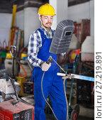 Купить «Smiling guy using welder for construction work», фото № 27219891, снято 17 января 2017 г. (c) Яков Филимонов / Фотобанк Лори