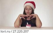 Купить «Beautiful happy teen girl in a Santa Claus hat dreams of a gift, receives a festive cake and expresses dissatisfaction on white background stock footage video», видеоролик № 27220207, снято 30 октября 2017 г. (c) Юлия Машкова / Фотобанк Лори