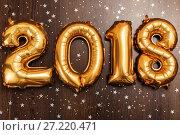 Купить «Bright metallic gold balloons figures 2018, Christmas, New Year Balloon with glitter stars on dark wood table background», фото № 27220471, снято 19 ноября 2017 г. (c) Сергей Тимофеев / Фотобанк Лори
