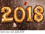 Купить «Bright metallic gold balloons figures 2018, Christmas, New Year Balloon with glitter stars on dark wood table background», фото № 27220479, снято 19 ноября 2017 г. (c) Сергей Тимофеев / Фотобанк Лори
