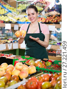 Купить «Friendly salesgirl standing near fresh fruits and vegetables in store», фото № 27221459, снято 14 октября 2017 г. (c) Яков Филимонов / Фотобанк Лори
