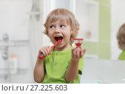 Купить «Happy child brushing teeth near mirror in bathroom. He is monitoring lasting of cleaning action with hourglass.», фото № 27225603, снято 20 ноября 2017 г. (c) Оксана Кузьмина / Фотобанк Лори