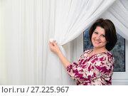 Купить «Woman puts tulle clamps on curtains in apartment», фото № 27225967, снято 22 ноября 2017 г. (c) Володина Ольга / Фотобанк Лори