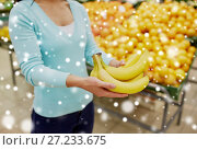 Купить «customer with bananas at grocery store», фото № 27233675, снято 2 ноября 2016 г. (c) Syda Productions / Фотобанк Лори
