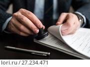 Купить «Бизнесмен ставит печать на документах», эксклюзивное фото № 27234471, снято 6 ноября 2017 г. (c) Игорь Низов / Фотобанк Лори