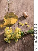 Купить «rapeseed oil (canola) and rape flowers on wooden table», фото № 27235315, снято 20 мая 2017 г. (c) Майя Крученкова / Фотобанк Лори