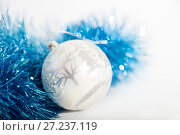 Купить «Christmas decorations of blue and silver color on a white background - ball and tinsel», фото № 27237119, снято 24 ноября 2017 г. (c) Юлия Бабкина / Фотобанк Лори