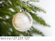 Купить «Christmas decorations, one white ball hanging on the Christmas tree», фото № 27237127, снято 25 ноября 2017 г. (c) Юлия Бабкина / Фотобанк Лори