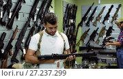 Купить «positive young men choosing air weapon in military shop», видеоролик № 27237299, снято 14 июля 2017 г. (c) Яков Филимонов / Фотобанк Лори