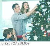 Купить «Family decorating Christmas tree at home», фото № 27238059, снято 24 февраля 2018 г. (c) Яков Филимонов / Фотобанк Лори