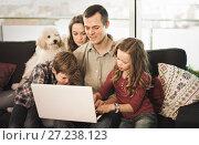 Купить «Young happy family watching movie on laptop together at home», фото № 27238123, снято 23 декабря 2016 г. (c) Яков Филимонов / Фотобанк Лори