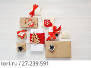 Mockup paper parcels wrapped tied with tags. A red heart and some christmas gift boxes wrapped with paper kraft and tied with red and white bakers twine on a white wooden table. Vintage Style. Стоковое фото, фотограф Happy Letters / Фотобанк Лори
