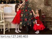 Купить «Две девочки в красных платьях наряжают елку», фото № 27240403, снято 17 декабря 2015 г. (c) Марина Володько / Фотобанк Лори